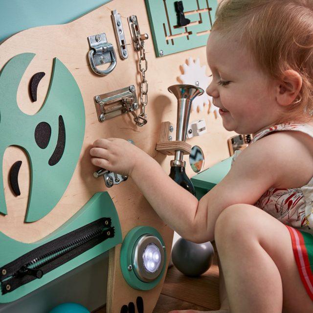 Dziecko bawiące się tablicą manipulacyjną Leniwiec